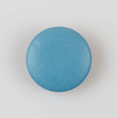 Guzik obciągany skórą naturalną w kolorze jasno niebieskim, śr. 38 mm