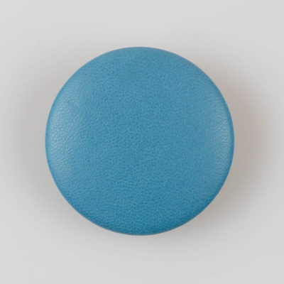 Guzik obciągany skórą naturalną w kolorze jasno niebieskim, śr. 44 mm