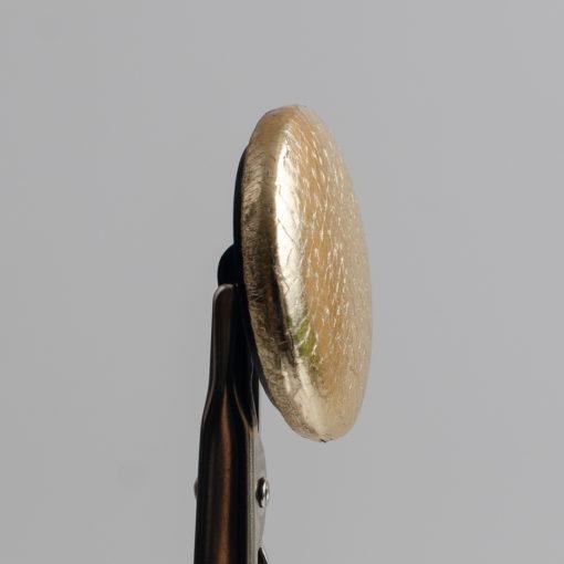 Guzik obciągany sztuczną skórą w kolorze złotym, śr. 28 mm (Defekt)