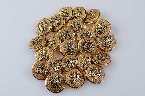Guzik ozdobny w stylu retro z herbem florystycznym - tribalowym w kolorze starego złota, średnica 25 mm.